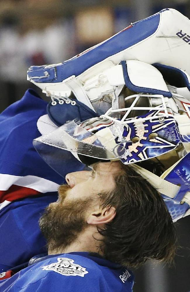 New York Rangers goalie Henrik Lundqvist (30) adjusts his mask during a timeout against the Los Angeles Kings in the third period during Game 4 of the NHL hockey Stanley Cup Final, Wednesday, June 11, 2014, in New York. The Rangers won the game 2-1