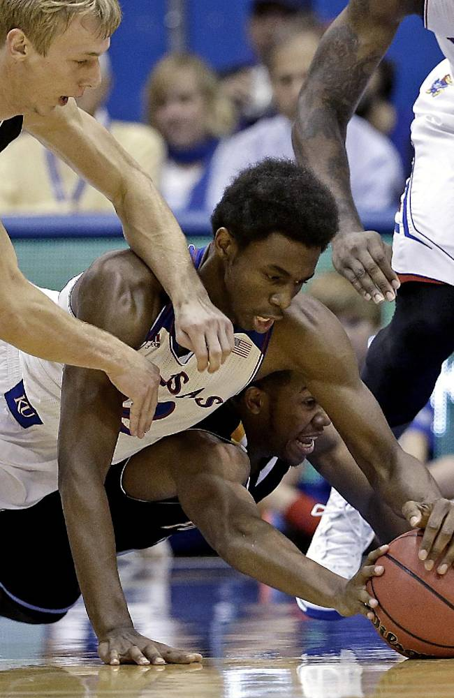 Kansas guard Andrew Wiggins, center, battles Fort Hays State's Craig Nicholson, bottom, and Jake Stoppel, top, for a loose ball during the first half of an exhibition NCAA college basketball game Tuesday, Nov. 5, 2013, in Lawrence, Kan
