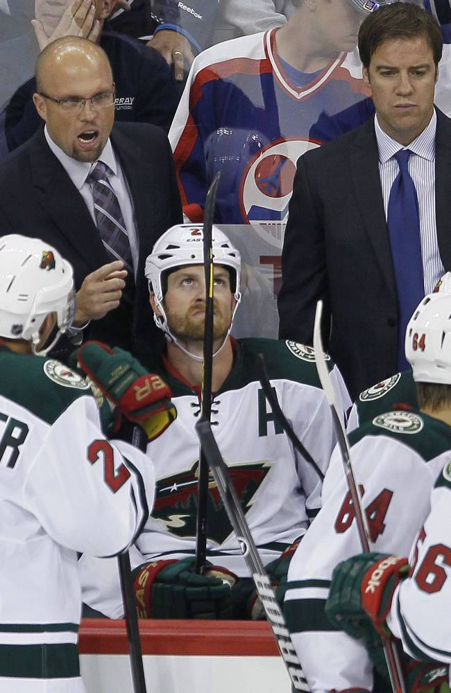 Minnesota Wild head coach Mike Yeo, upper left, talks to his team during third-period preseason NHL hocky game action against the Winnipeg Jets in Winnipeg, Manitoba, Thursday, Sept. 19, 2013