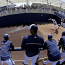 Players watch as Milwaukee Brewers starting pitcher Matt Garza warms up before an exhibition spring training baseball game against the San Diego Padres Friday, March 7, 2014, in Phoenix The Associated Press