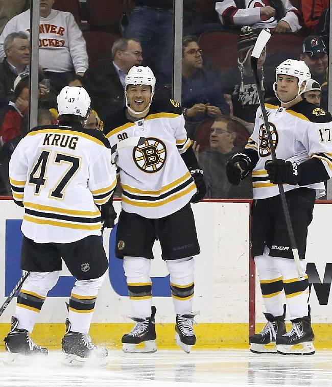 Boston Bruins defenseman Torey Krug (47), right wing Jarome Iginla (12) and left wing Milan Lucic (17) celebrate a goal by Iginla against the New Jersey Devils during the second period of an NHL hockey game, Tuesday, March 18, 2014, in Newark, N.J