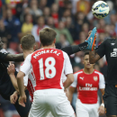 Hull City's Mohamed Diame, left, kicks the ball as his teammate Abel Hernandez jumps to control the ball during the English Premier League soccer match between Arsenal and Hull City at the Emirates stadium in London Saturday, Oct. 18, 2014