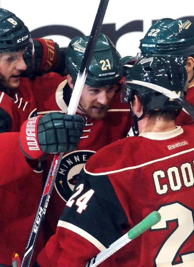 Minnesota Wild teammates huddle around Kyle Brodziak, center, who scored the first goal of the game in the second period,  as the Minnesota Wild played the Calgary Flames at Xcel Energy Center in St. Paul, Minn. on Monday,  March 3, 2014. From left are Marco Scandella, Brodziak, Matt Cooke and Nino Niederreiter