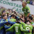 Seattle Sounders' Marco Pappa, second from left, is doused with water as he is mobbed by teammates, including Osvaldo Alonso, upper center, after Pappa scored his second goal of an MLS soccer match against the Los Angeles Galaxy, Saturday, Oct. 25, 2014,
