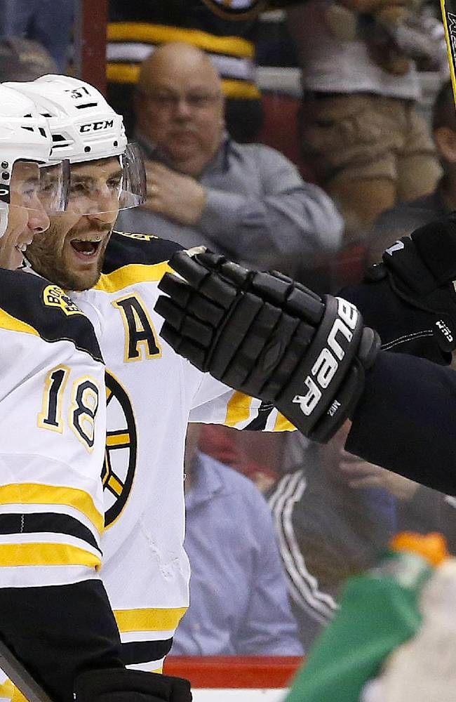 Boston Bruins' Patrice Bergeron, second from left, celebrates his goal against the Phoenix Coyotes with teammates Reilly Smith (18) and Andrej Meszaros (41), of the Czech Republic, during the first period of an NHL hockey game on Saturday, March 22, 2014, in Glendale, Ariz