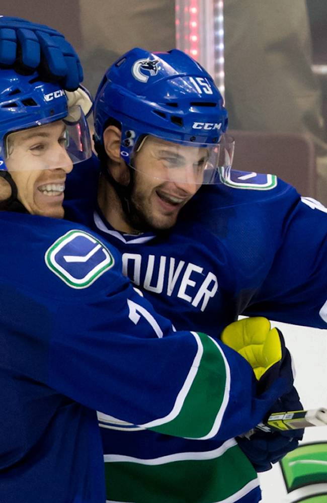 Vancouver Canucks' David Booth, left, and Brad Richardson celebrate Richardson's goal against the Los Angeles Kings during the third period of an NHL hockey game Saturday, April 5, 2014, in Vancouver, British Columbia. Vancouver won 2-1