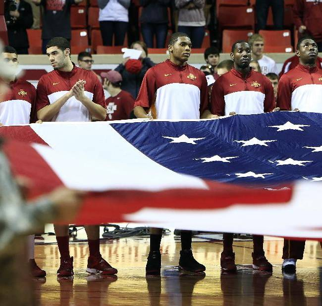 Iowa State members help hold the American flag before the start of an NCAA college basketball game against Oklahoma in Norman, Okla. on Saturday, Jan. 11, 2014