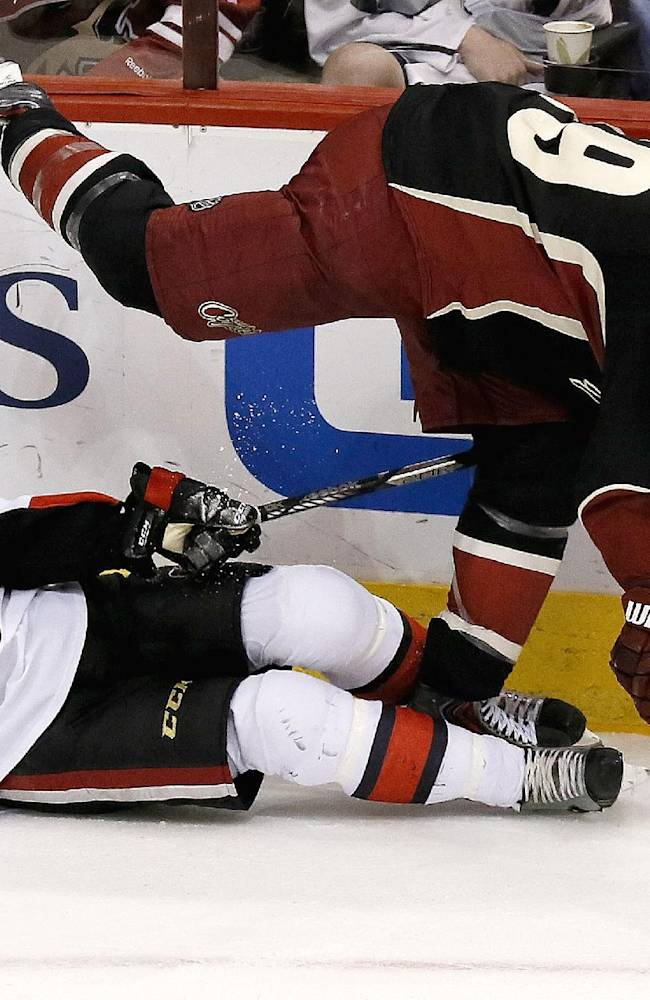 Ottawa Senators' Erik Condra, left, takes a skate to the face from Phoenix Coyotes' Shane Doan (19) during the third period in an NHL hockey game on Tuesday Oct. 15, 2013, in Glendale, Ariz.  The Senators defeated the Coyotes 4-3 in overtime