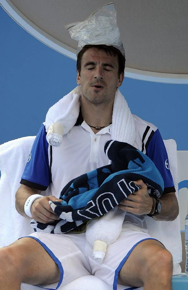 Tommy Robredo of Spain cools down with ice pack on his head during his second round match against Julien Benneteau of France at the Australian Open tennis championship in Melbourne, Australia, Wednesday, Jan. 15, 2014