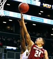 Boston College's Olivier Hanlan (21) goes up for a layup as VCU's Rob Brandenberg defends during the first half of an NCAA college basketball game Saturday, Dec. 28, 2013, in New York. (AP Photo/Rich Schultz)