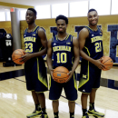 Michigan guard Caris Levert (23), Derrick Walton Jr., (10) and Zak Irvin (21) pose during the men's NCAA college basketball media day in Ann Arbor, Mich., Thursday, Oct. 30, 2014. (AP Photo/Carlos Osorio)