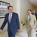 Duke men's basketball coach Mike Krzyzewski, left, walks to the Senate chamber with state Sen. Andrew C. Brock for a joint session of the North Carolina General Assembly on Tuesday, May 19, 2015 in Raleigh, N.C. The joint session passed SJR 714, honoring Duke's national championship. (John Joyner/The Herald-Sun via AP)