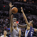 San Antonio Spurs' Tony Parker (9) lays the ball up against the Memphis Grizzlies' Courtney Lee (5) and Zach Randolph during the first quarter of an NBA basketball game Sunday, April 6, 2014, in San Antonio The Associated Press