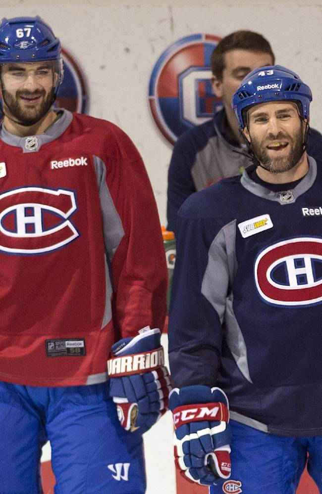 Montreal Canadiens left wing Max Pacioretty, left, and defenseman Mike Weaver take part in NHL hockey practice Friday, May 16, 2014 in Brossard, Quebec. The Canadiens host the New York Rangers in Game 1 of the Eastern Conference final in the Stanley Cup playoffs on Saturday in Montreal