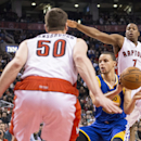 Golden State Warriors Stephen Curry lays off a pass between Toronto Raptors' Tyler Hansbrough, left, and Kyle Lowry during the first half of an NBA basketball game Sunday, March 2, 2014, in Toronto The Associated Press