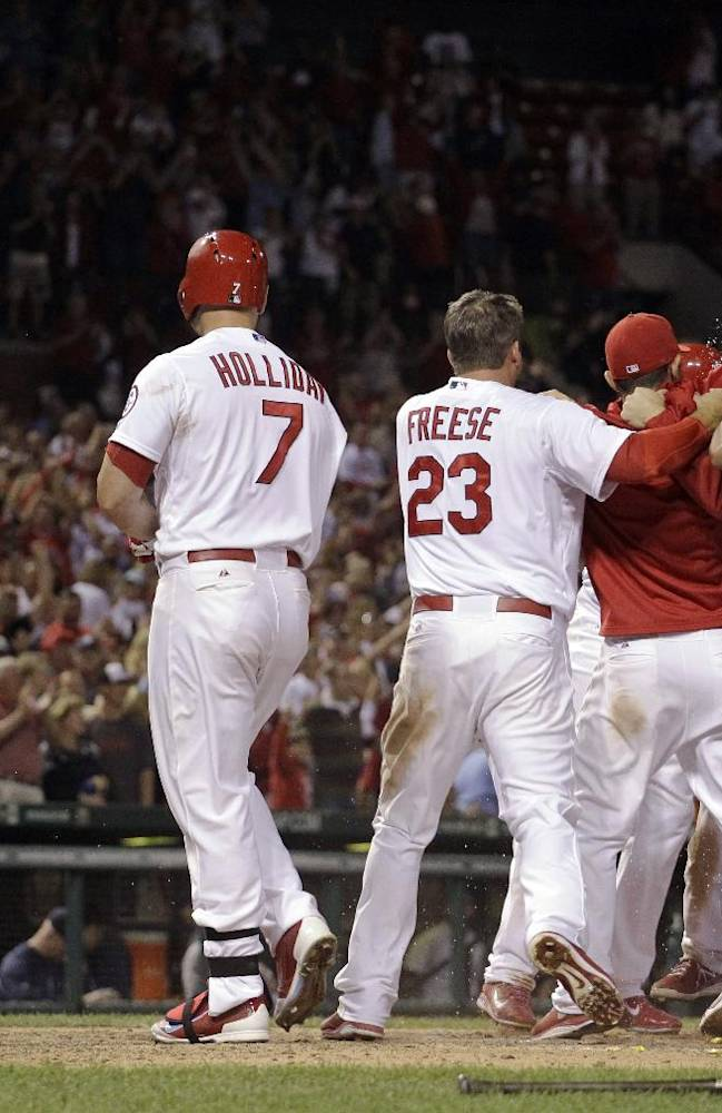 Seattle Mariners relief pitcher Oliver Perez, left, walks off the field as St. Louis Cardinals congratulate Pete Kozma after Kozma scored the game-winning run on a passed ball during the 10th inning of a baseball game Friday, Sept. 13, 2013, in St. Louis. The Cardinals won 2-1