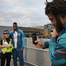Miami Dolphins' Jared Odrick, right, takes a picture of his teammate Cameron Wake with a British police officer on her request, shortly after the team's arrival at London's Gatwick Airport, England, Friday, Sept. 26, 2014. The Miami Dolphins will play the