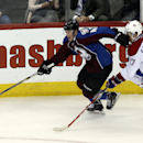 Colorado Avalanche defenseman Tyson Barrie, left, picks up a loose puck along boards as he skates past Montreal Canadiens center Alex Galchenyuk in the third period of the Canadiens' 4-3 victory in an NHL hockey game in Denver on Monday, Dec. 1, 2014 The
