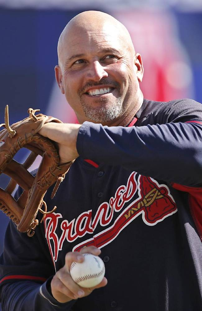 Atlanta Braves manager Fredi Gonzalez throws on the field before a spring exhibition baseball game against the New York Yankees in Tampa, Fla., Sunday, March 16, 2014