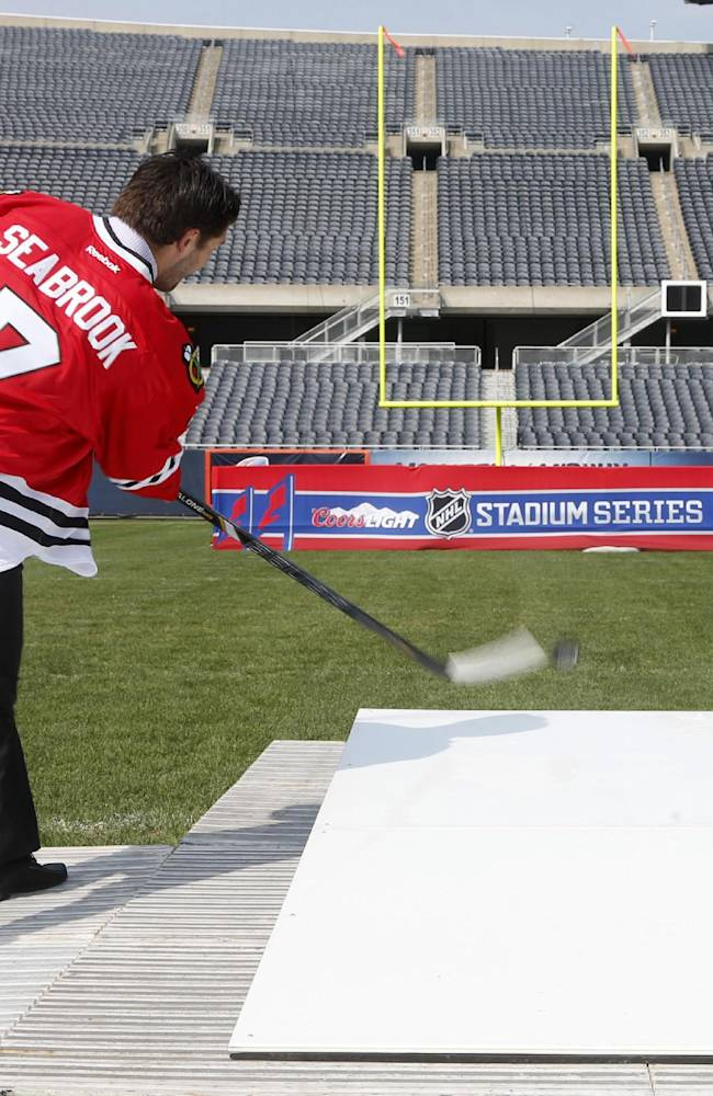 Chicago Blackhawks' Brent Seabrook shoots a puck from the 40-yard line, 150 feet from the goal post, at Soldier Field as part of a promotion for the Stadium Series hockey game between the Blackhawks and Pittsburgh Pengiuns next March, Thursday, Sept. 19, 2013, in Chicago