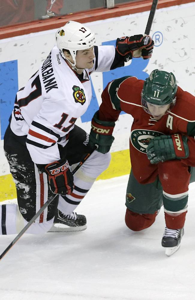 Chicago Blackhawks' Sheldon Brookbank, left, slows up Minnesota Wild's Zach Parise  in a chase for the puck in the first period of an NHL hockey game, Thursday, Jan. 23, 2014, in St. Paul, Minn. It was Parise's first return to the lineup following recovery of a broken foot