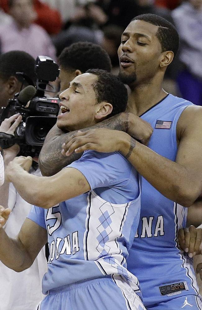 North Carolina's Marcus Paige and Leslie McDonald, right, celebrate Paige's shot in overtime to beat North Carolina State 85-84 in an NCAA college basketball game in Raleigh, N.C., Wednesday, Feb. 26, 2014