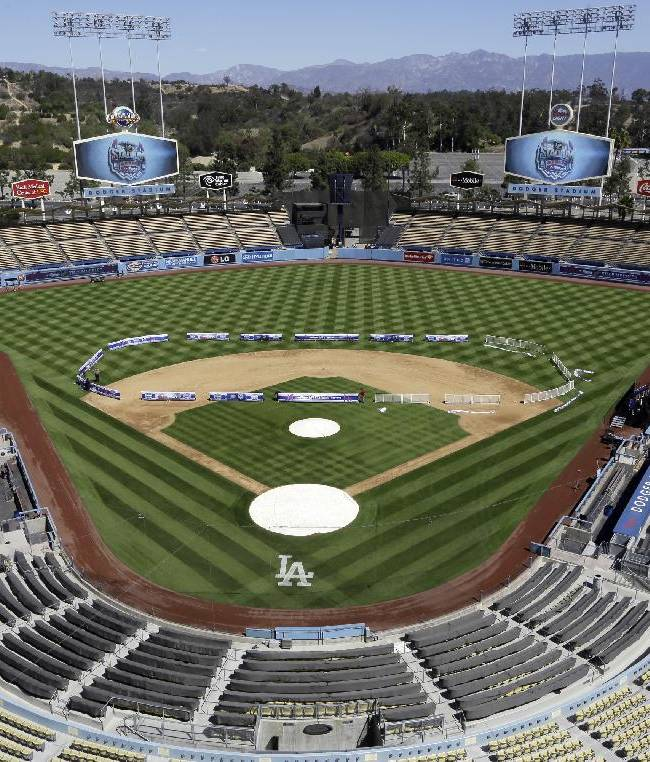 Workers install banners in the shape of a hockey rink before an NHL news conference Thursday, Sept. 26, 2013, at Dodger Stadium in Los Angeles, announcing the outdoor hockey game between the Los Angeles Kings and Anaheim Ducks. The game will be played on a temporary rink on the baseball field on Jan. 25, 2014