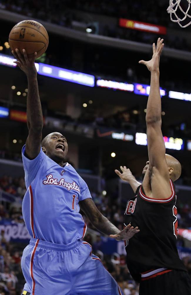 Los Angeles Clippers guard Jamal Crawford, left, shoots over Chicago Bulls forward Taj Gibson during the first half of an NBA basketball game in Los Angeles, Sunday, Nov. 24, 2013