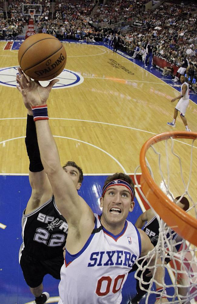 Philadelphia 76ers' Spencer Hawes (00) goes up for a rebound against San Antonio Spurs' Tiago Splitter (22), of Brazil, during the first half of an NBA basketball game, Monday, Nov. 11, 2013, in Philadelphia