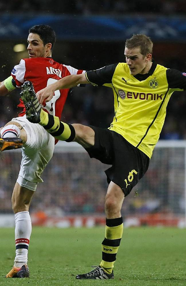 Arsenal's Mikel Arteta, left, and Dortmund's Sven Bender battle for the ball during the Champions League Group F soccer match between Arsenal and Borussia Dortmund at the Emirates Stadium in London Tuesday, Oct. 22, 2013