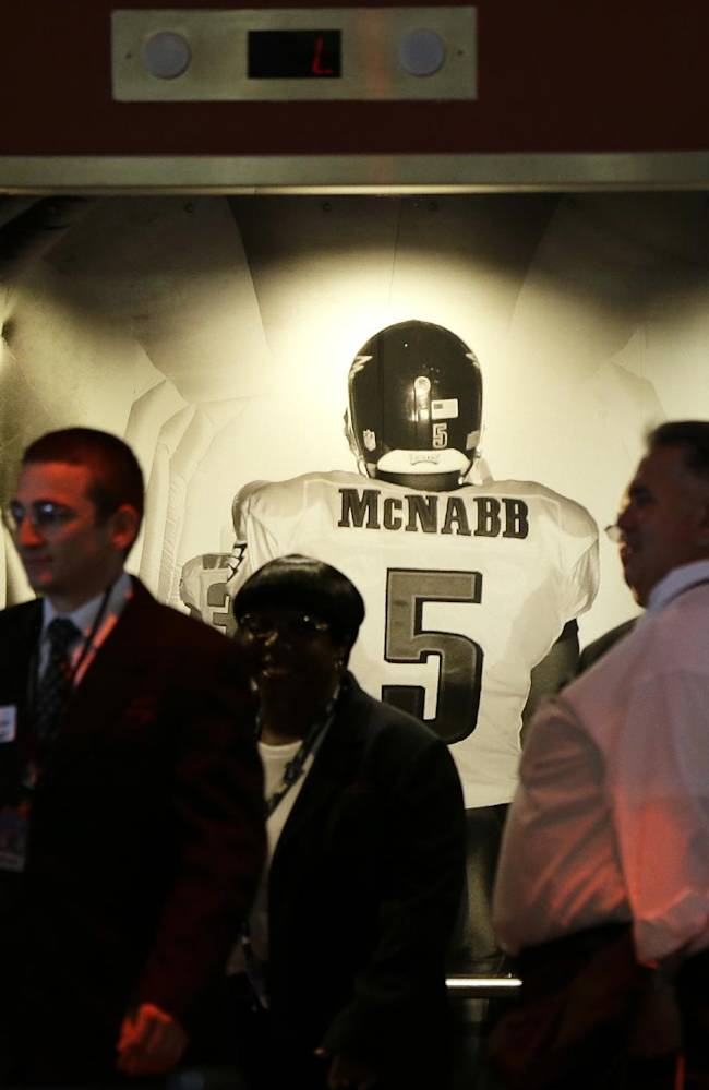 People exit an elevator past a photo mural of former Philadelphia Eagles quarterback Donovan McNabb before the Eagles' NFL football game against the Kansas City Chiefs, Thursday, Sept. 19, 2013, in Philadelphia. McNabb is scheduled to have his jersey retired at halftime