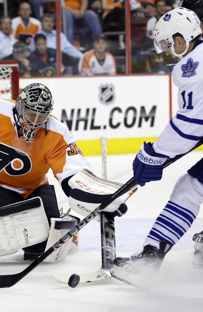 Philadelphia Flyers' Steve Mason, left, blocks a shot by Toronto Maple Leafs' Jay McClement during the first period of an NHL hockey game on Wednesday, Oct. 2, 2013, in Philadelphia, Pa