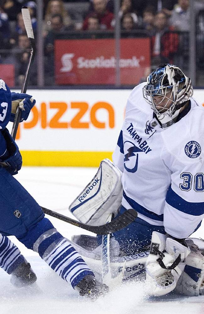 Tampa Bay Lightning goaltender Ben Bishop covers the post as Toronto Maple Leafs defenseman Dion Phaneuf looks for a rebound during second period NHL action in Toronto on Wednesday, March 19, 2014