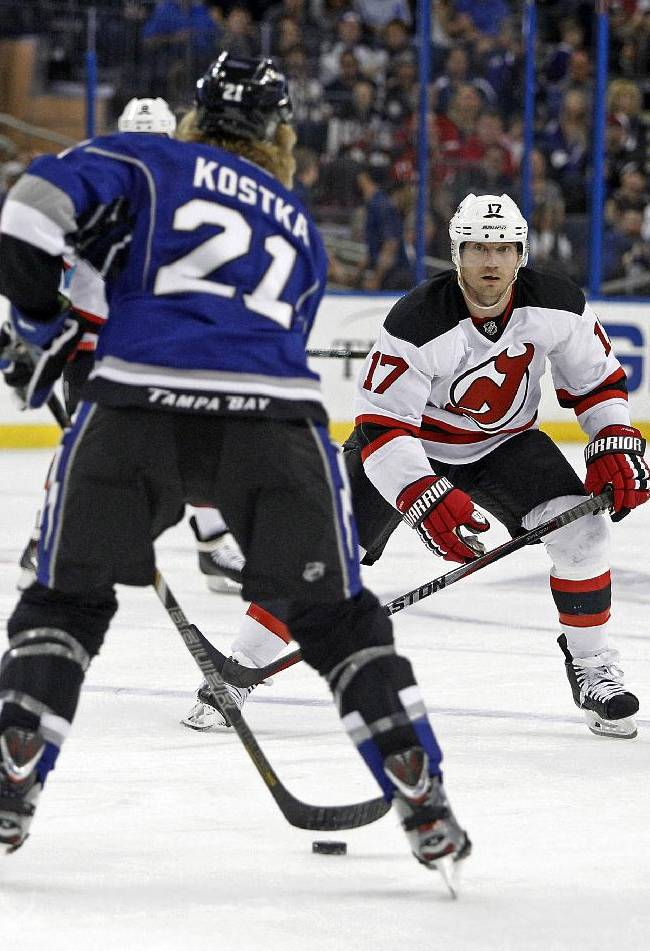 Tampa Bay Lightning defenseman Michael Kostka (21) defends the puck from New Jersey Devils right wing Michael Ryder (17) during the first period of an NHL hockey game Saturday, March 15, 2014, in Tampa, Fla