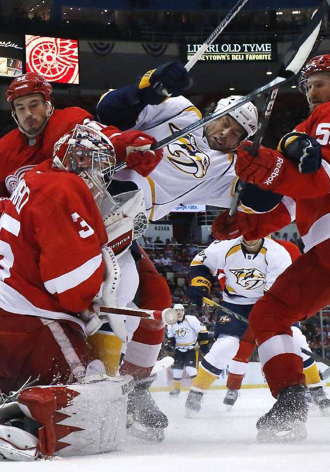 Nashville Predators center David Legwand (11) is checked by Detroit Red Wings defenseman Jonathan Ericsson (52), of Sweden, and Niklas Kronwall (55), of Sweden, as  goalie Jimmy Howard (35) makes a stop during an NHL hockey game in Detroit, Tuesday, Nov. 19, 2013. Nashville won 2-0