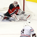 New Jersey Devils goalkeeper Keith Kinkaid (1) blocks a shot by Chicago Blackhawks right wing Marian Hossa, bottom, of Slovakia, during the overtime period of an NHL hockey game, Tuesday, Dec. 9, 2014, in Newark, N.J. The Blackhawks won 3-2 The Associated