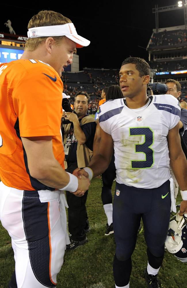 In this Aug. 18, 2012, file photo, Denver Broncos quarterback Peyton Manning (18) shakes hands with Seattle Seahawks quarterback Russell Wilson (3) following an NFL football preseason game in Denver. The easiest decision in the NFL is forking up the big bucks to sign Peyton Manning, Tom Brady or Drew Brees. The majority of teams pay their starting quarterbacks just a fraction of the base salaries of the Mannings, Brady and Jay Cutler, who makes $17.5 million this season. Cheap doesn't mean inferior. Andrew Luck has taken the Colts to the playoffs in each of his two seasons, and Russell Wilson has already won a championship with the Seahawks in his first two years