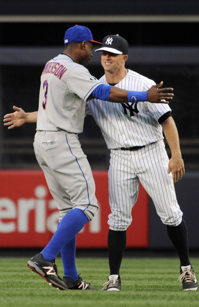 New York Mets' Curtis Granderson, left, greets New York Yankees' Brett Gardner in the outfield before a baseball game against the New York Yankees at Yankee Stadium on Monday, May 12, 2014, in New York