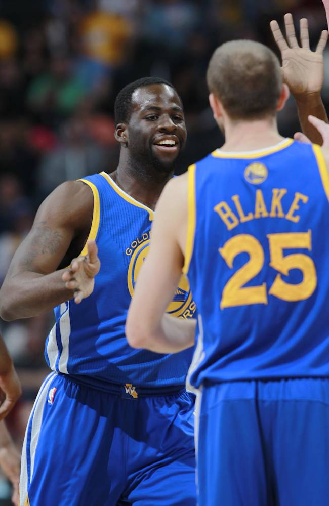 Golden State Warriors forward Draymond Green, back, is congratulated by guard Steve blake after Green's shot to move the Warriors ahead by five points against the Denver Nuggets late in the fourth quarter of the Warriors' 116-112 victory in an NBA basketball game in Denver on Wednesday, April 16, 2014