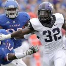 TCU running back Waymon James (32) pushes Kansas cornerback Greg Brown (5) away as he runs for a gain during the first half of an NCAA college football game, Saturday, Sept. 15, 2012, in Lawrence, Kan. (AP Photo/Charlie Riedel)