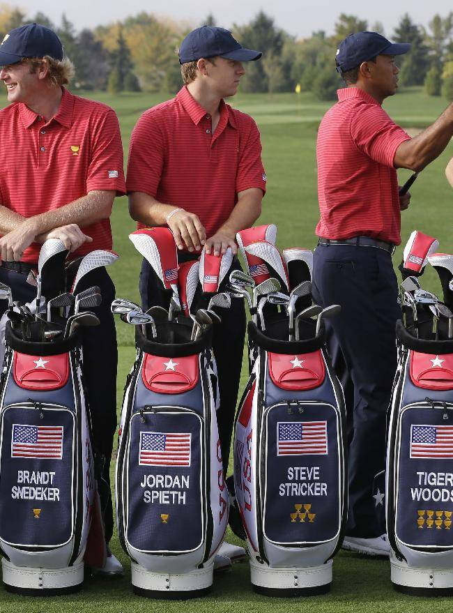 United States team player Brandt Snedeker, left, Jordan Spieth, middle, and Tiger Woods wait for a team photo before a practice round during a practice round for the Presidents Cup golf tournament at Muirfield Village Golf Club Wednesday, Oct. 2, 2013, in Dublin, Ohio