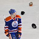 Edmonton Oilers' Taylor Hall (4) reacts after scoring a hat trick and fans throw their hats onto the ice surface during third period NHL hockey action in Edmonton, Alberta, Thursday, Dec. 5, 2013 The Associated Press