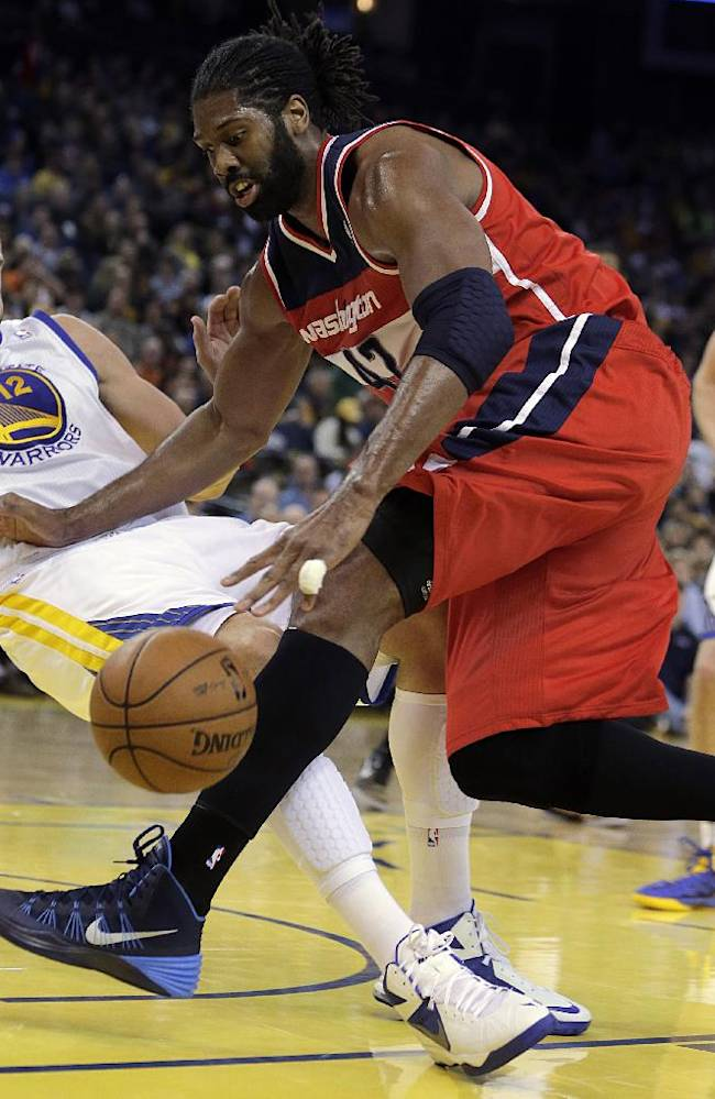 Washington Wizards' Nene Hilario, right, drives the ball into Golden State Warriors' Andrew Bogut (12) during the first half of an NBA basketball game, Tuesday, Jan. 28, 2014, in Oakland, Calif