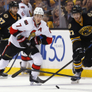 Boston Bruins' Dougie Hamilton (27) knocks the stick out of the hands of Ottawa Senators' Kyle Turris during the third period of the Senators 3-2 shootout win in a shootout in an NHL hockey game in Boston Saturday, Dec. 13, 2014 The Associated Press