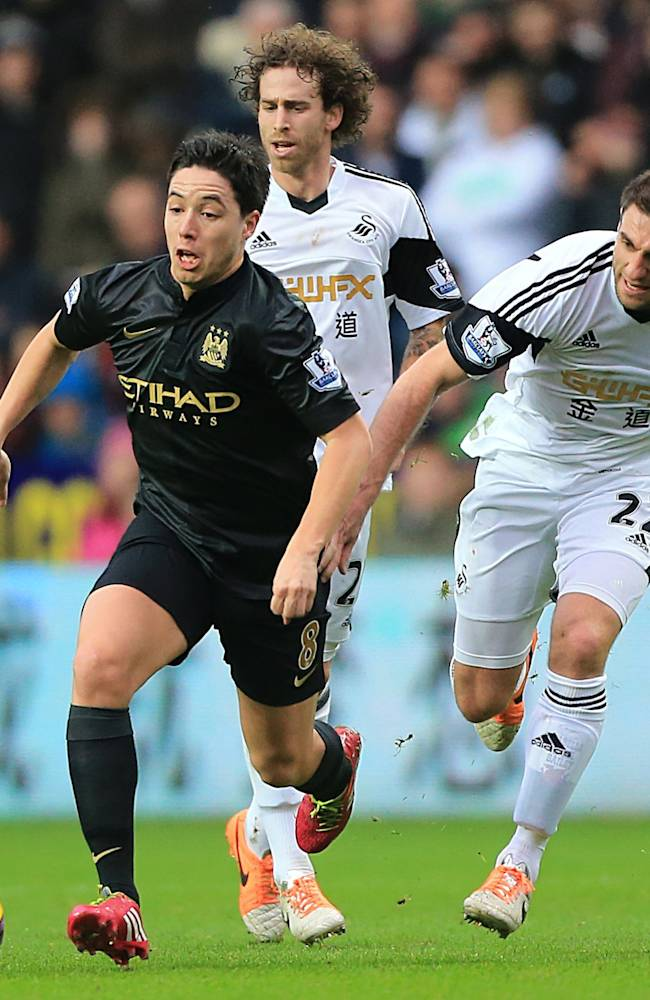 Swansea City's Angel Rangel, right, and Manchester City's Samir Nasri battle for the ball during their English Premier League soccer match at the Liberty Stadium, Swansea, Wales, Wednesday Jan. 1, 2014