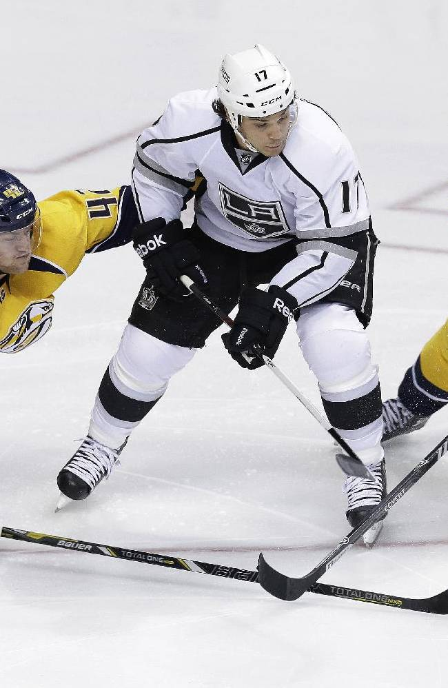 Nashville Predators defenseman Mattias Ekholm (42) and forward Patric Hornqvist (27), both of Sweden, keep the puck away from Los Angeles Kings left wing Daniel Carcillo (17) in the third period of an NHL hockey game Thursday, Oct. 17, 2013, in Nashville, Tenn. The Kings won 2-1 in a shootout