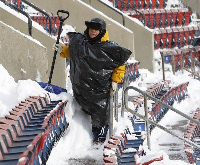 In this Dec. 20, 2009 file photo, workers clean snow from Giants Stadium prior to the start of an NFL game between the New York Jets and Atlanta Falcons, in East Rutherford, N.J. Instead of shrinking from the possibility that football's ultimate championship could be played in a blizzard, organizers of the first outdoor, cold-climate Super Bowl have decided to embrace the snow as the game's unofficial theme. In fact, some officials are positively hoping for snow