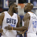 Charlotte Bobcats' Anthony Tolliver, right, holds back Al Jefferson, left, as Jefferson reacts after being called for a technical foul during the second half of an NBA basketball game against the Orlando Magic in Charlotte, N.C., Friday, April 4, 2014. Th