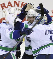 Vancouver Canucks' Alexander Edler, left, and Dan Hamhuis celebrate with goaltender Roberto Luongo after they defeated the New Jersey Devils 3-2 in a shootout during an NHL hockey game on Thursday, Oct. 24, 2013, in Newark, N.J. (AP Photo/Bill Kostroun)