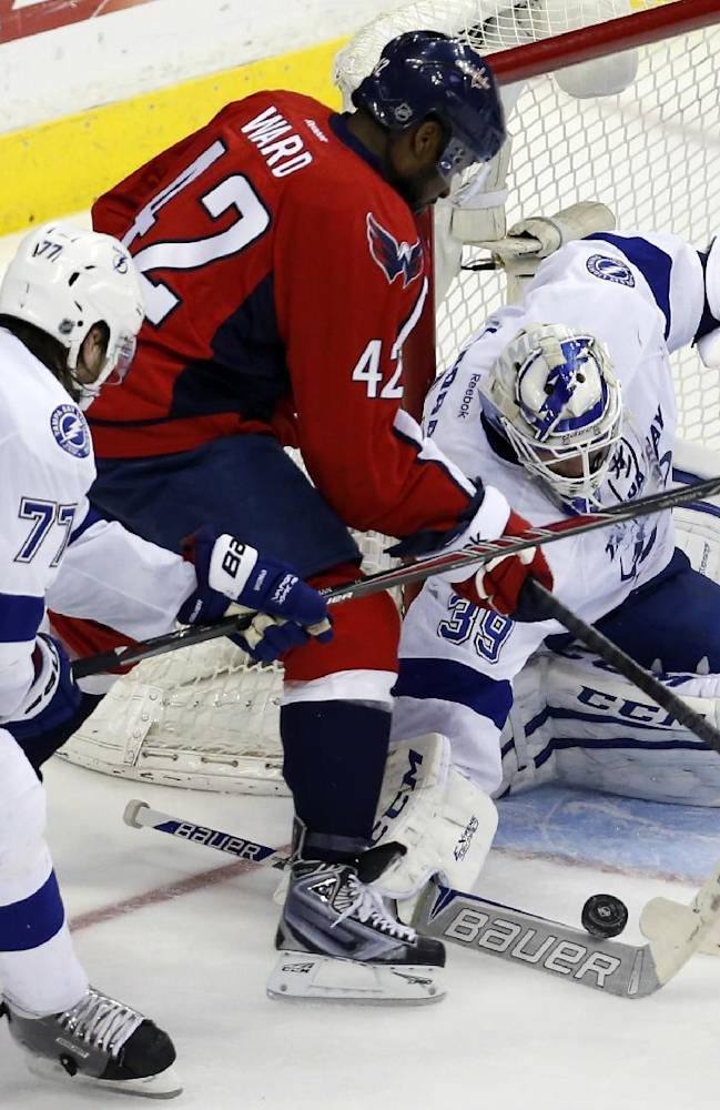 Tampa Bay Lightning goalie Anders Lindback (39), from Sweden, reaches to knock the puck away from Washington Capitals right wing Joel Ward (42) with the help of defenseman Victor Hedman (77), also from Sweden, in the third period of an NHL hockey game on Sunday, April 13, 2014, in Washington. The Lightning won 1-0 in a shootout